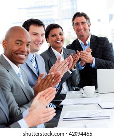 Team of successful multi-ethnic business people applauding in a conference