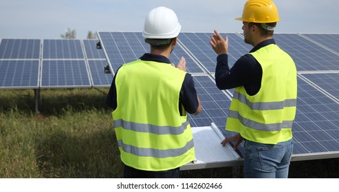 team of Supervisor Engineers Men Talking Planning Teamwork Activity in Solar Panels Power Farm, Photovoltaic Cell Park, Green Energy Concept