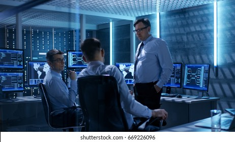Team of Technical Moderators Have Discussion in Monitoring Room. System Control Room is full of Working Displays and Has Servers Racks.