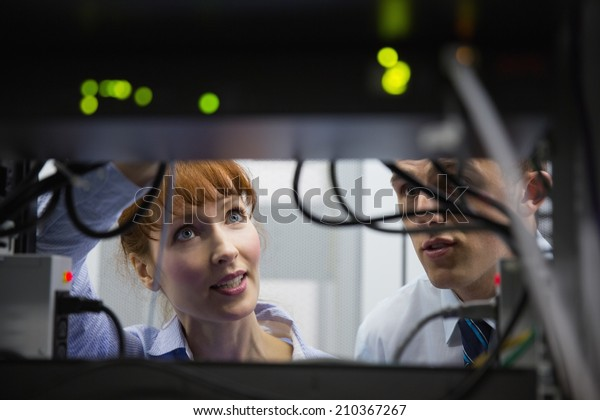 Team of technicians talking and looking at server in large data center
