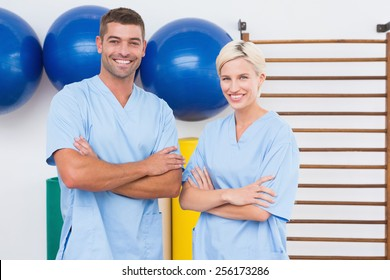 Team of therapists with arms crossed smiling at camera in fitness studio
