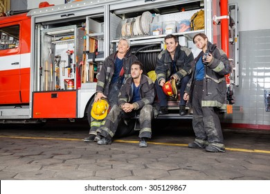 Team of thoughtful firefighters looking away by firetruck at station