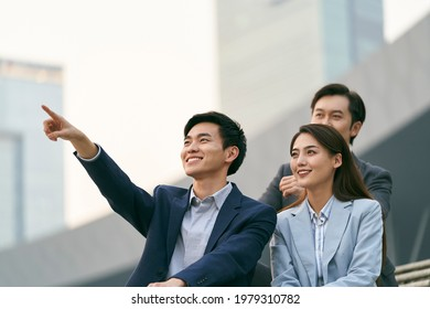 team of three asian corporate executives talking chatting relaxing outdoors