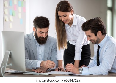 Team of three business people sitting at the table with several documents and discussing important questions