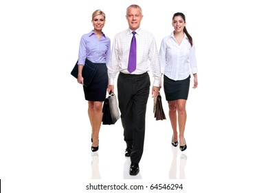 A team of three business people walking towards camera, isolated on a white background.
