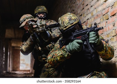 Team of three soldiers in uniform training in the building with weapon/Three soldiers during training in the building