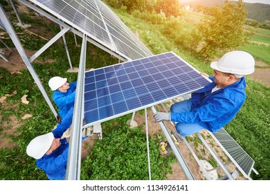 Team of three technicians mounting photo voltaic panel to stand-alone solar system platform on bright sunny day. Alternative energy, professionally done job and financial investment concept.