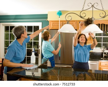 Team of three women housekeepers / maids cleaning a modern kitchen. Maid on the left is pointing, reminding the maid with the extension pole duster not to miss a spot.