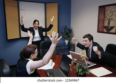 Team of three work colleagues with their arms raised in celebration