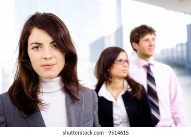Team of three young business people lining up for portrait, smiling businesswoman in front.