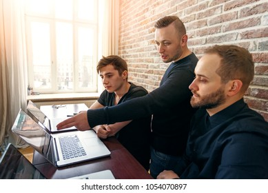 Team of three young men working in the office. Group of coders looking for creative decision directing by team leader.