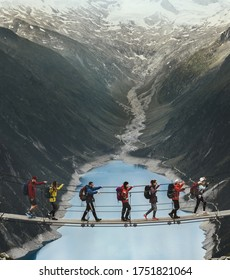 Team of travelers with a backpack in the mountains. A group of travelers crosses a suspension bridge against the backdrop of a mountain and a glacier. Travel and active life concept.