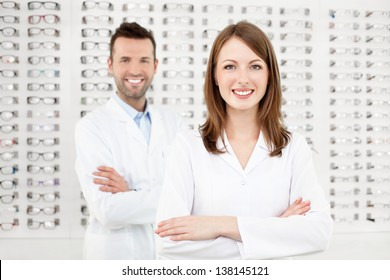 Team of two eye doctors, opticians or optometrists standing in optical shop.
