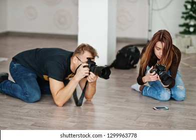 The team of two photographers shooting on studio at knees. Professional photographer on work. Master class.