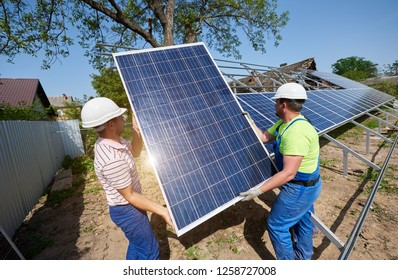 Team of two technicians working on exterior voltaic solar panel system installation in rural countryside on bright sunny summer day. Renewable ecological cheap green energy production concept.