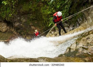 Team Of Two Young Women Wearing Waterproof Equipment Descending A Waterfall