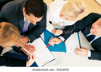 Team - two young workers and two senior people -  working hard, discussing contractual documents or spreadsheets