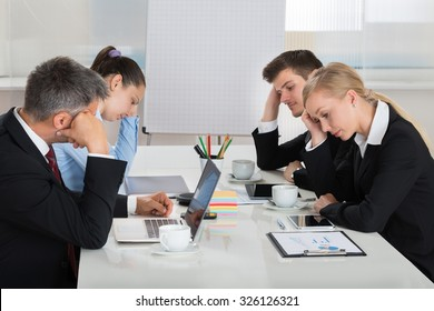 Team Of Unhappy Businesspeople Sitting In Business Meeting