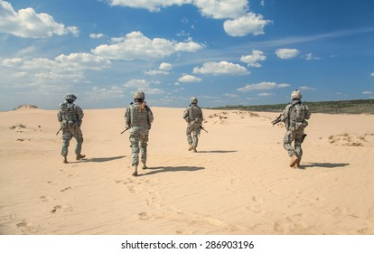 Team of United states airborne infantry men with weapons moving patrolling desert. Sand and blue sky on background of squad, sunlight, back view