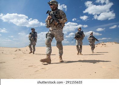 Team of United states airborne infantry men with weapons moving patrolling desert. Sand and blue sky on background of squad, sunlight, low angle view