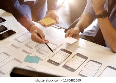 Team ux designer creative graphic planning application development a prototype smartphone layout.