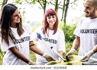 Team of volunteers cleaning wood from trash