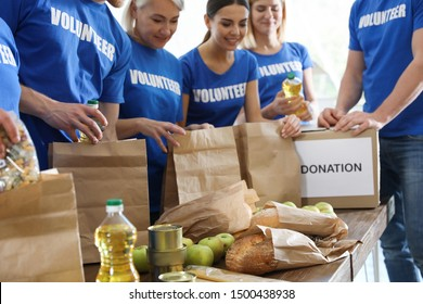 Team of volunteers collecting food donations at table, closeup