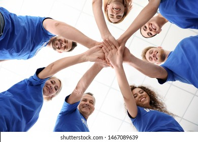 Team of volunteers putting their hands together on light background, bottom view