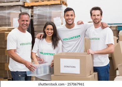 Team of volunteers smiling at camera in a large warehouse