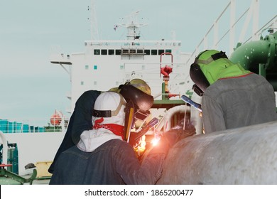 Team Welder is Welding pipe on Oil tanker ship in shipyard accommodation bridge deck background