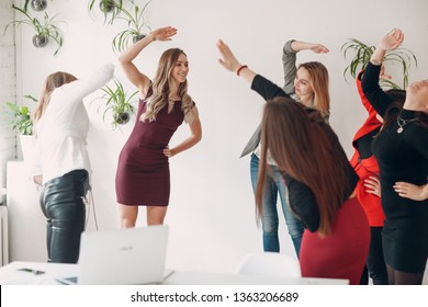 Team women doing exercises in office. Exercising females at work. Benefits of fitness for employees and managers.
