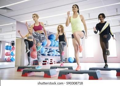Equipo de mujeres con clase de aeróbic escalonado