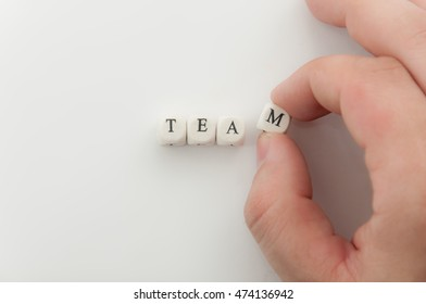 Team word spelled by dice. Fingers hold M letter. Focus on dice with TEA letters