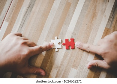 Team work concept, Hands hold puzzles on wooden table