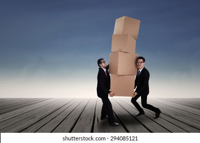 Team work concept; Two Asian business men carrying heavy boxes
