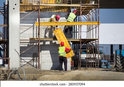 Team work at construction site, workers passing metal formworks on scaffolds