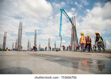 Team work of Construction worker in safety standard uniform Concrete pouring during commercial concreting floors of building in construction site and Civil Engineer or safety officer inspec work