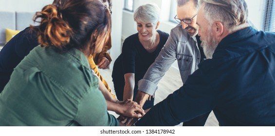 Team work and cooperation concept, people staking their hands on top of each other and smiling. Business people joining hands showing unity.