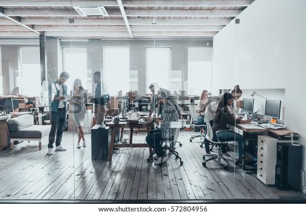 Team bei der Arbeit. Gruppe junger Geschäftsleute in intelligentem Freizeitbekleidung, die in Kreativbüros zusammenarbeiten