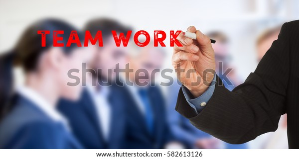 Team work, Male hand in business wear holding a thick pen, writing on an imaginary screen at the camera, business team in background, digital composing.