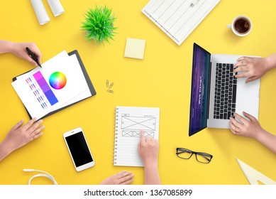 Team work on web design project. Top view, flat lay scene with laptop, smart phone, plans, papers and coffee. Yellow desk.