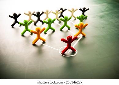 Team work organizational chart concept, colorful dolls on blackboard.