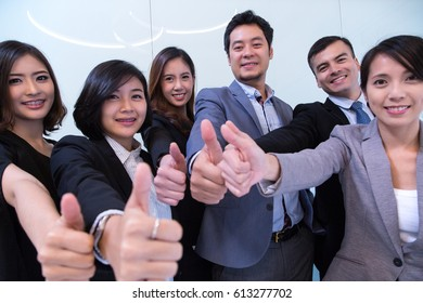 Team work thumb up together in meeting room.