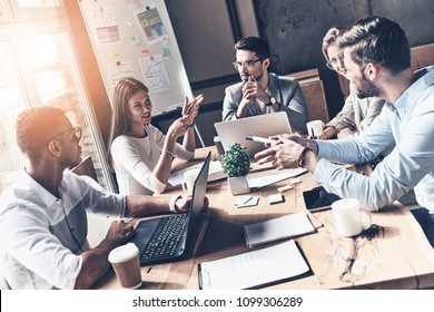 Team at work. Top view of young modern people in smart casual wear discussing business while working in the creative office