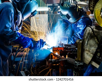 Team worker with protective mask welding metal