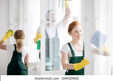Team of workers cleaning white office windows wearing yellow gloves and protective clothing