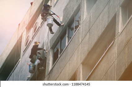 Team of workers painting wall high rise building. Painters are painting  exterior office building with roller. Dangerous jobs in the building, cleaning and maintenance industries. High risk work.