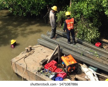 Team of workers pull the concrete pillars out of the water on the iron pontoon. River coast reconstruction, Thailand