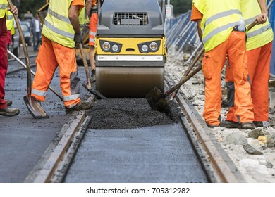 Team of workers put the hot asphalt on a street along tram car's railroad lines. Small steamroller. Road construction workers with shovels in protective uniforms. Working in the hot day.