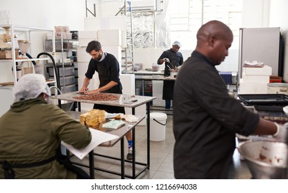 Team of workers in various stages of the chocolate production process working together in an artisanal chocolate making factory